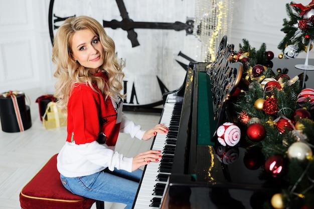 Une jolie jeune femme vêtue d'un pull de noël joue du piano et sourit contre un grand cadran et un décor de noël. Photo Premium