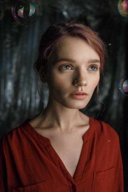 Jolie jeune fille caucasienne en chemise rouge lève les yeux. des bulles de savon volent autour de sa tête, chatoyantes aux couleurs de l'arc-en-ciel. Photo Premium