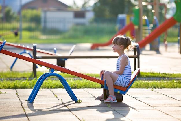Jolie jeune fille enfant à l'extérieur sur une balançoire à bascule sur une journée d'été ensoleillée. Photo Premium