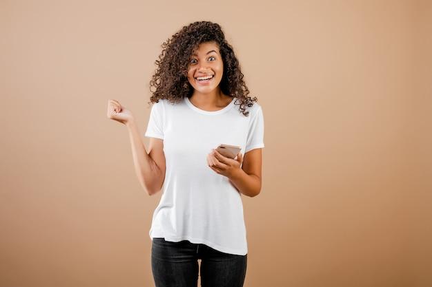 Jolie jeune fille noire avec téléphone à la main, isolée sur le marron Photo Premium
