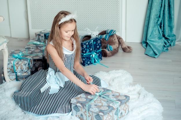 Jolie jeune fille ouvre des cadeaux dans la salle de décoration de noël. tonique Photo Premium