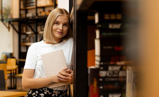 Jolie Jeune Fille Posant à La Bibliothèque Photo gratuit
