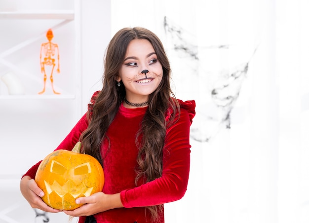 Jolie jeune fille tenant une citrouille sculptée Photo gratuit
