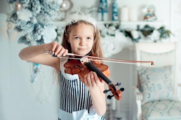 Jolie jeune fille avec violon dans la salle de décoration de noël. Photo Premium