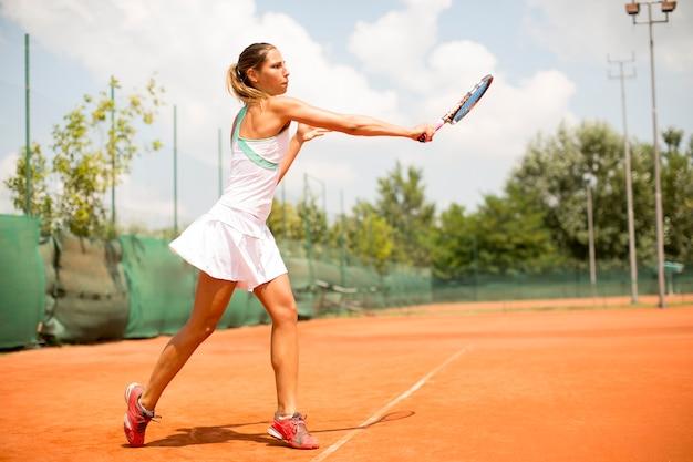 Jolie joueuse de tennis jouant sur le terrain par une journée ensoleillée Photo Premium