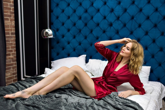 Jolie Mannequin Blonde Sensuelle Allongée Sur Le Lit, Profitez De Sa Matinée à L'hôtel De Luxe, Vêtue D'une Chemise De Nuit Et D'un Peignoir En Soie Bordeaux, De Cheveux Aveugles Et D'un Visage De Beauté, Style Boudoir. Photo gratuit