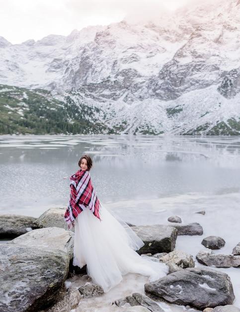 Jolie Mariée Couverte De Couverture Est Debout Sur Le Rocher Près Du Lac Gelé Entouré De Montagnes Photo gratuit