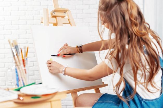 Jolie peintre peintre sur chevalet Photo Premium