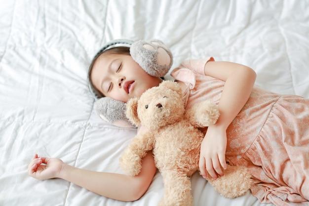 Jolie petite fille asiatique portant des manchons d'hiver avec ours en peluche couché sur le lit à la maison Photo Premium