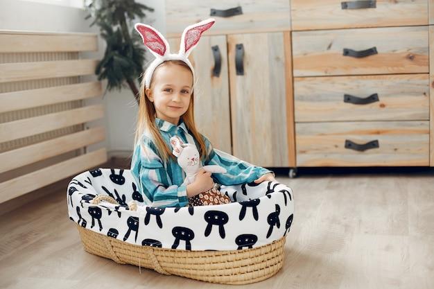 Jolie petite fille assise à la maison Photo gratuit