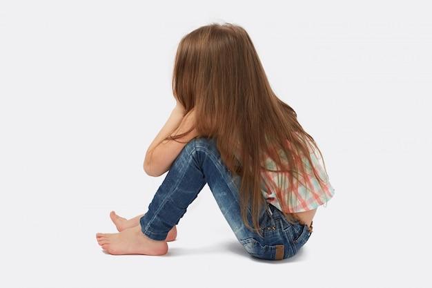 Jolie petite fille assise sur le sol Photo Premium