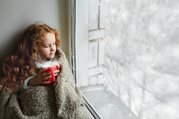Jolie petite fille assise avec une tasse de chocolat chaud près de la fenêtre et regardant la première neige qui tombe Photo Premium