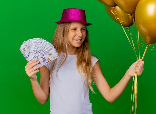 Jolie Petite Fille Au Chapeau De Vacances Tenant De L'argent Photo gratuit