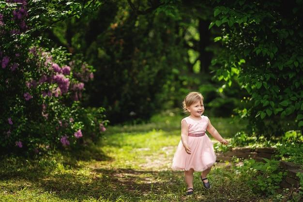 Jolie Petite Fille Aux Beaux Jours. Petite Fille Aux Cheveux Blonds En Robe Rose Souriant Parmi Les Arbres En Fleurs. Photo Premium