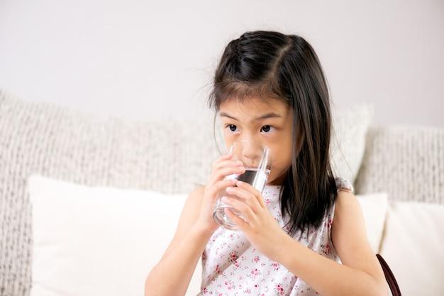 Jolie petite fille boit de l'eau sur le canapé à la maison. concept de soins de santé Photo Premium