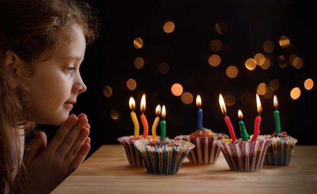 Jolie petite fille avec un chapeau de fête à la recherche d'un des bougies sur les gâteaux d'anniversaire. Photo Premium