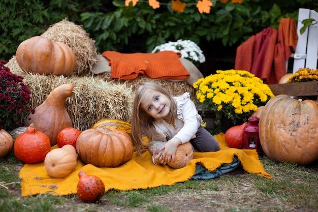Jolie petite fille avec citrouille en plein air Photo Premium