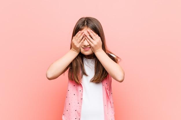 Jolie petite fille couvre les yeux avec les mains, sourit largement attend une surprise. Photo Premium