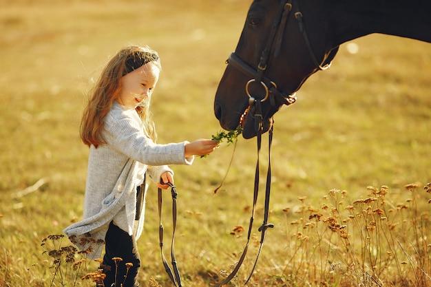 Jolie petite fille dans un champ d'automne avec cheval Photo gratuit