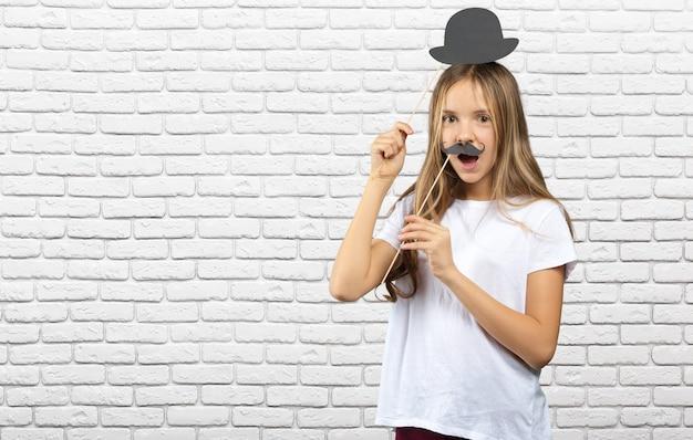 Jolie petite fille dans un papier avec des accessoires photo drôles. enfant heureux Photo Premium