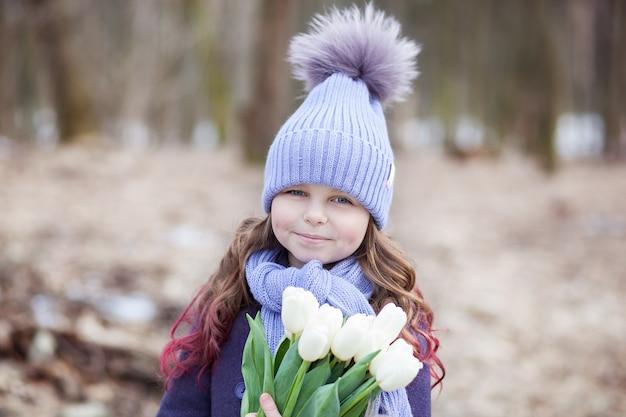Jolie Petite Fille Dans Le Parc Avec Un Bouquet De Tulipes Blanches. Des Fleurs En Cadeau Pour La Fête Des Mères Des Femmes. 8 Mars. Pâques. Fille Avec Un Bouquet Pour La Fête Des Mères Heureuse. Fait Un Cadeau Pour Ta Maman. Photo Premium