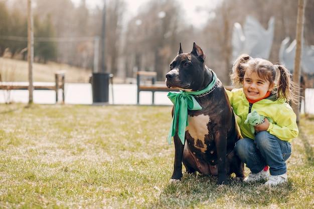 Jolie petite fille dans le parc avec un chien Photo gratuit