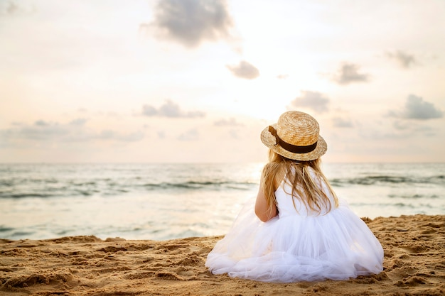 Jolie Petite Fille De Derrière Avec De Longs Cheveux Blonds Dans Un Chapeau De Paille Et Une Robe Blanche En Tutu Assis Photo Premium