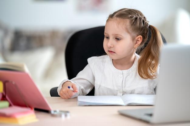 Jolie Petite Fille, Faire Ses Devoirs, écrire Dans Un Cahier, Utiliser Un Ordinateur Portable, E-learning Photo Premium