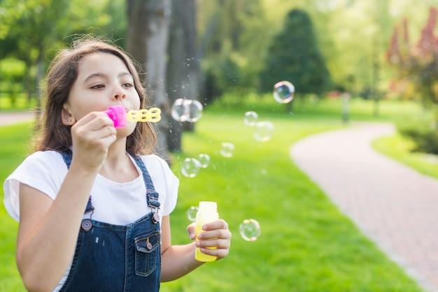 Jolie petite fille faisant des bulles de savon Photo gratuit