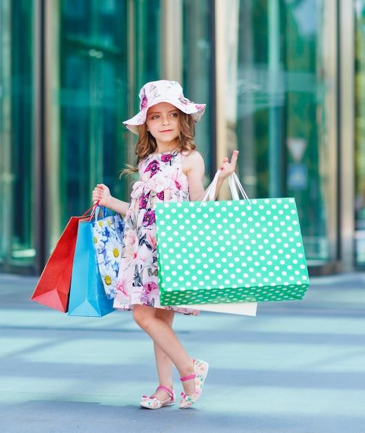 Jolie Petite Fille Faisant Du Shopping, Portrait D'un Enfant Avec Des Sacs à Provisions, Shopping, Fille. Photo Premium