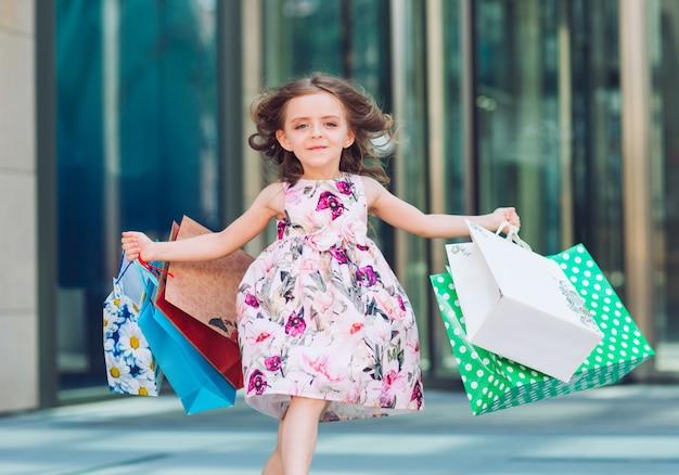 Jolie Petite Fille En Faisant Les Magasins. Portrait D'un Enfant Avec Des Sacs à Provisions. Achats. Fille. Photo Premium