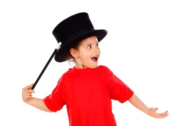 Jolie petite fille faisant de la magie avec un chapeau haut de forme et une baguette magique Photo Premium