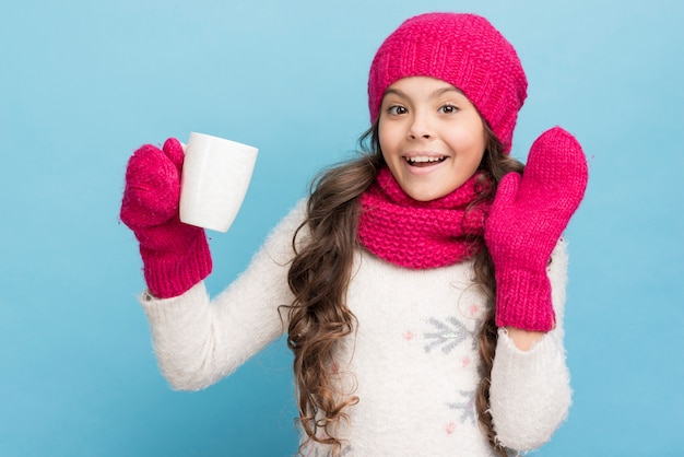 Jolie petite fille avec des gants et un chapeau tenant une tasse Photo gratuit