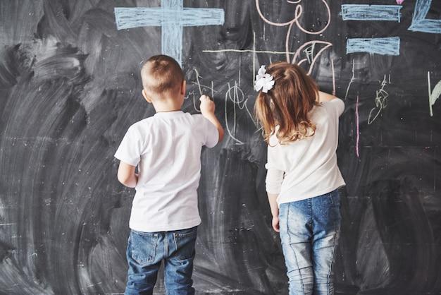 Jolie petite fille et garçon dessinant avec des couleurs de crayon sur le mur. travail d'enfant. mignon élève écrit sur un tableau Photo Premium