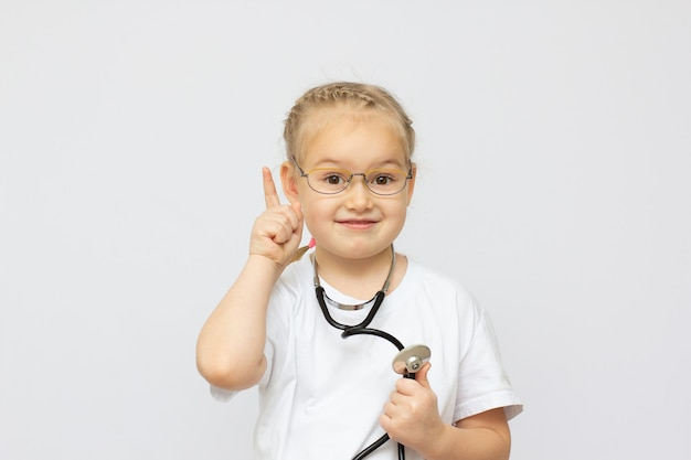 Jolie Petite Fille Habillée Comme Un Médecin Regardant La Caméra Avec Un Sourire Joyeux Doigt Vers Le Haut Photo Premium