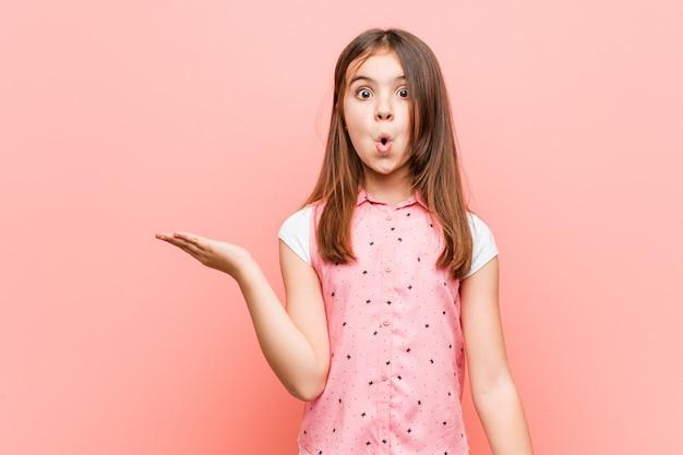 Jolie petite fille impressionnée par l'espace de copie sur la paume Photo Premium