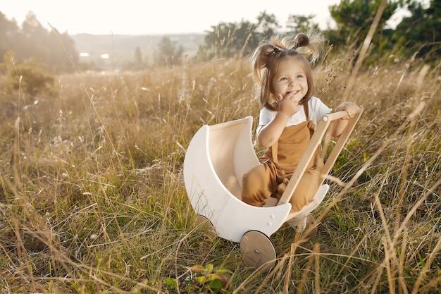 Jolie Petite Fille Jouant Dans Un Parc Avec Chariot Blanc Photo gratuit