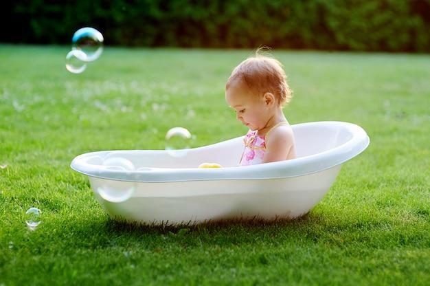 Jolie petite fille jouant avec de l'eau dans une petite baignoire en plastique à l'extérieur dans le jardin Photo Premium
