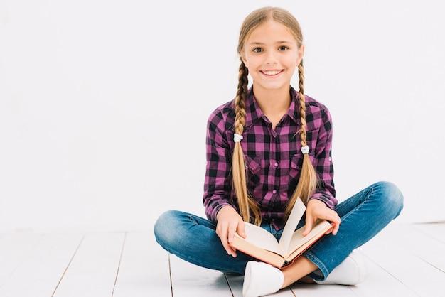 Jolie petite fille lisant un livre assis sur le sol Photo gratuit