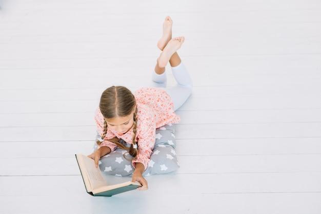 Jolie petite fille lisant un livre Photo gratuit