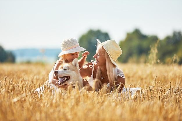 Jolie Petite Fille Avec Maman Et Chien Sur Champ De Blé. Heureuse Jeune Famille Profiter Du Temps Ensemble à La Nature Photo Premium