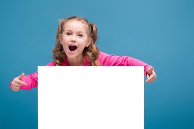 Jolie petite fille mignonne en chemise rose avec un singe et un pantalon bleu tenir affiche vide Photo Premium
