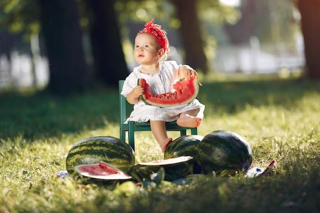 Jolie petite fille avec des pastèques dans un parc Photo gratuit