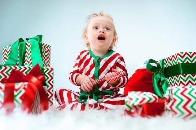 Jolie Petite Fille Près Du Bonnet De Noel Posant Sur Fond De Noël Avec Décoration. Assis Sur Le Sol Avec Boule De Noël. Photo gratuit