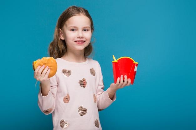 Jolie petite fille en pull aux cheveux bruns tient un hamburger Photo Premium