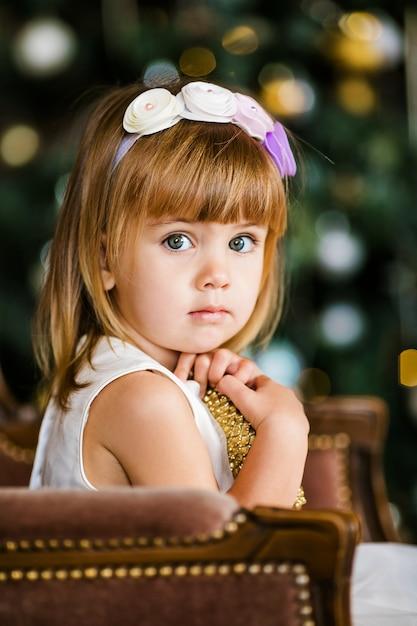 Jolie petite fille à la robe blanche avec une belle couronne près du sapin de noël Photo Premium