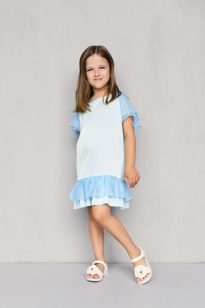 Jolie Petite Fille En Robe Bleue Et Sandales Blanches Posant Près Du Mur Gris Photo Premium