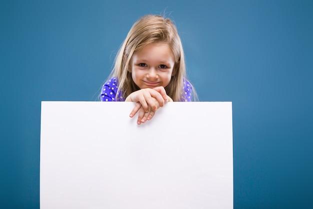 Jolie petite fille en robe violette est titulaire d'une affiche vide Photo Premium