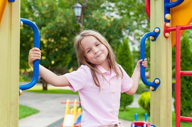 Jolie petite fille s'amuser sur une aire de jeux en plein air en journée d'été ensoleillée. loisirs sains actifs et sports de plein air pour les enfants. Photo Premium