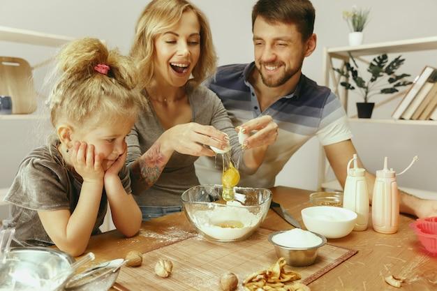 Jolie Petite Fille Et Ses Beaux Parents Préparent La Pâte Pour Le Gâteau Dans La Cuisine à La Maison. Concept De Mode De Vie Familial Photo gratuit